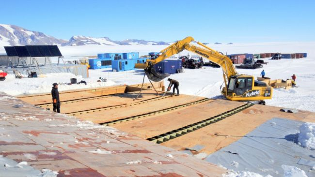 BELARE team members using a Komatsu Crane to tear down the old garage to make room for a new one - © International Polar Foundation