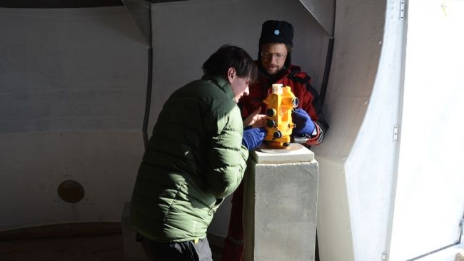 Stephen Bracke gets a hand from engineer Johnny Gaelens as he takes measurements of Earth's magnetic field in the shelter the station team set up this season for the GEOMAG project. - © International Polar Foundation / Alain Hubert