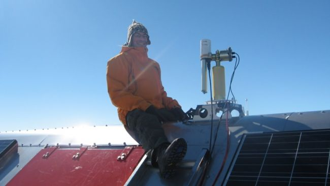 Dr. Alexander Mangold setting up an instrument on the roof of PEA - © International Polar Foundation