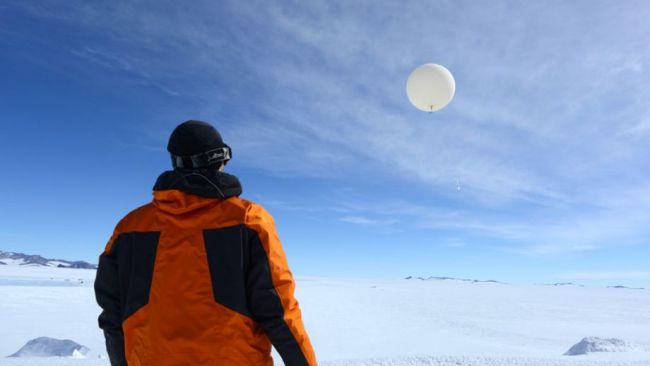 Quentin Laffineur releases a meteorological balloon at Princess Elisabeth station, which will record data as it rises into the stratosphere - © International Polar Foundation / Jos van Hemelrijck
